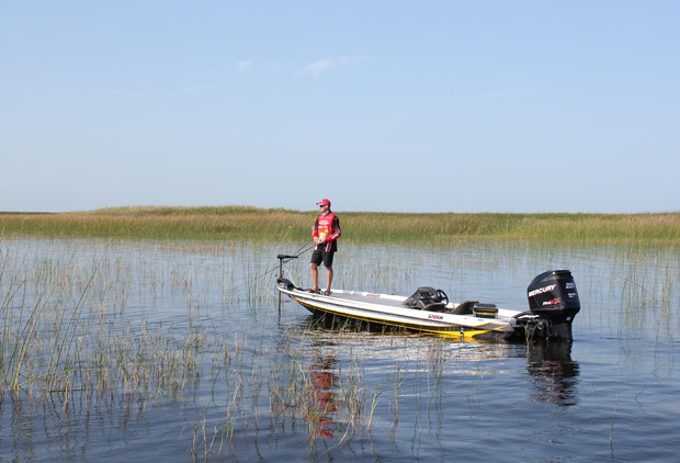 man working trolling motor on front of bass boat in lake