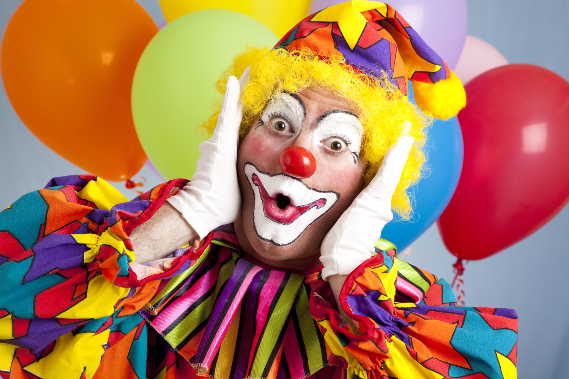 Colorful male clown standing in front of balloons