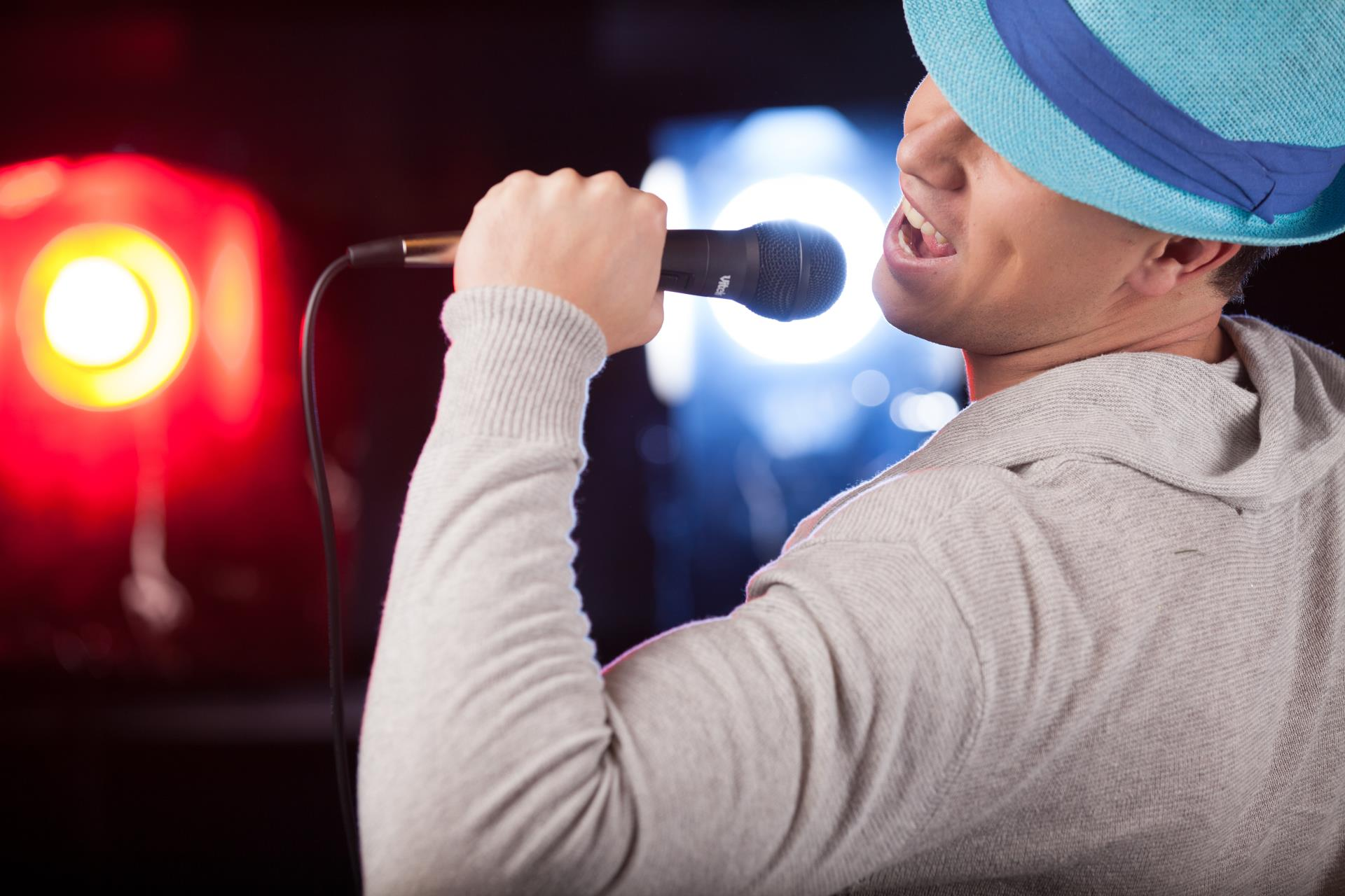 man singing into microphone with blue fedora