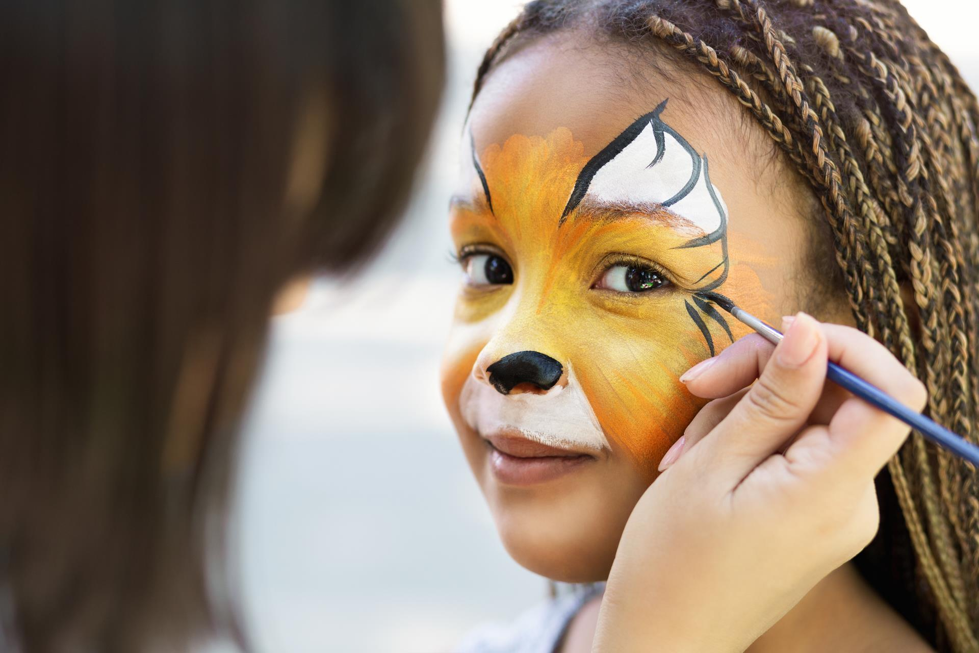 child having face painted like a tiger